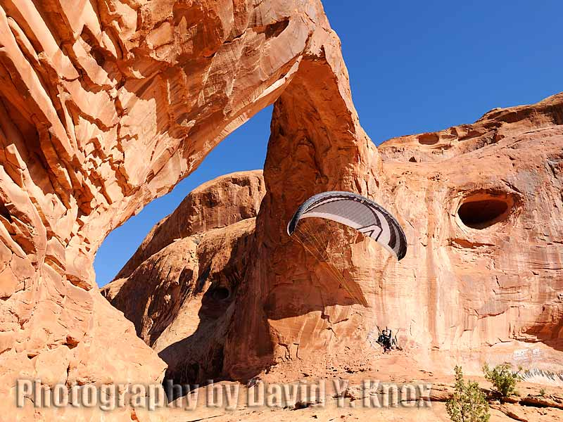 The photographer flying his paramotor through Corona Arch. Moab Area, Utah, USA.